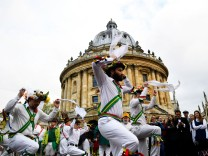 Morris dancers perform during May Day celebrations outside Radcliffe Camera as the sun rises over Oxford