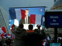 President Elect Emmanuel Macron is seen on a giant screen near the Louvre museum after results were announced in the second round vote of the 2017 French presidential elections