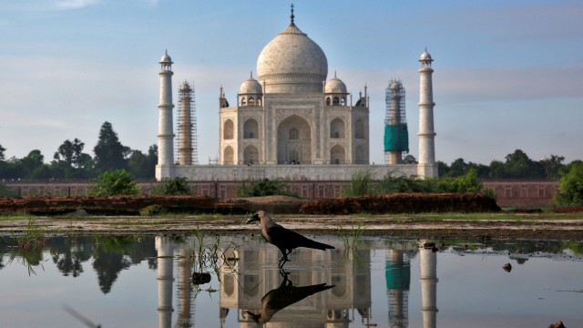 The Taj Mahal is reflected in a puddle in Agra