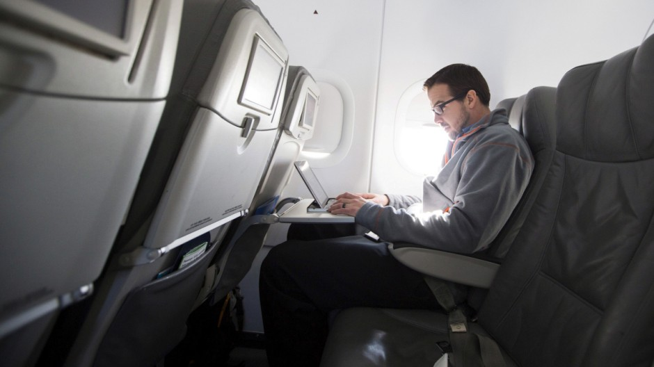 FILE PHOTO: A man uses his laptop to test a new high speed inflight Internet service named Fli-Fi while on a special JetBlue media flight out of John F. Kennedy International Airport in New York, file
