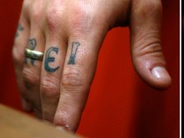 A combination of two pictures shows the hands of defendant Andre E. sporting tattoos reading 'free dom' after his arrival in the courtroom in Munich