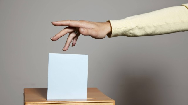 Eine junge Frau bei einer Wahl in der Wahlzelle Stimmabgabe in der Demokratie McPBBO McPBBO