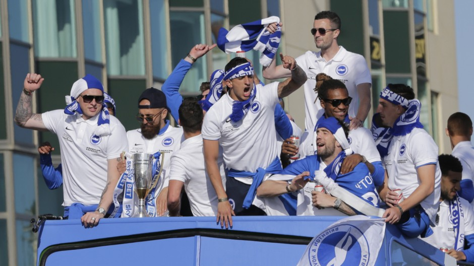 Brighton's Bruno celebrates with the trophy and team mates atop of the open top bus during the parade through Brighton
