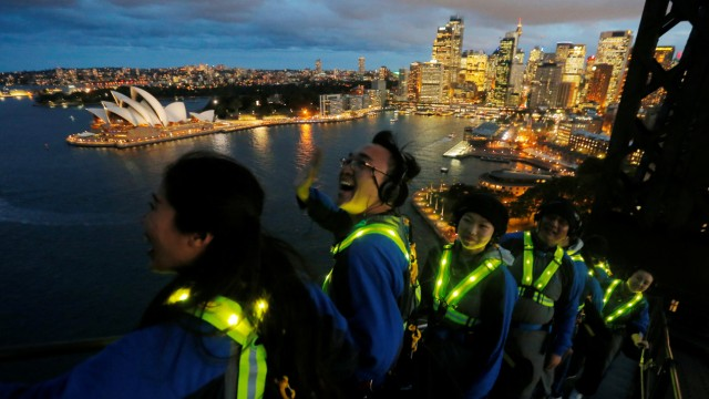 Participants wear glowing vests as they look out to the Sydney Opera House from the Sydney Harbour Bridge in Australia during a press preview of the Vivid Climb Mandarin for Chinese-language tours of the Sydney icon
