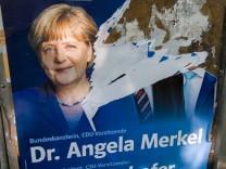 Abgerissenes Wahlplakat mit Angela Merkel