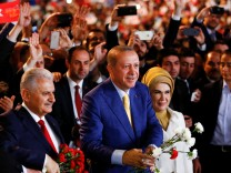 Turkish President Tayyip Erdogan, accompanied by his wife Emine Erdogan and Prime Minister Binali Yildirim, greets members of his party during the Extraordinary Congress of the ruling AKP in Ankara