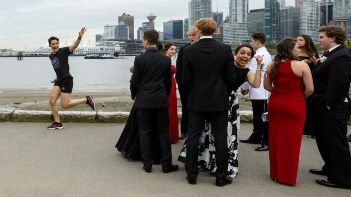 Prime Minister Justin Trudeau jogs past a group of high school students dressed for their prom in Vancouver
