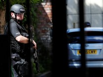 An armed police officer stands outside a residential property near to where a man was arrested in the Chorlton area of Manchester