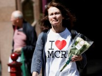 A woman lays flowers for the victims of the Manchester Arena attack, in central Manchester