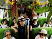 Passengers react inside a plant-filled bus, a special route that runs for 5 days, featuring the concept of integrating more green space into cities, in Taipei , Taiwan