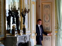 French President Emmanuel Macron walks out of his office at the Elysee Palace in Paris