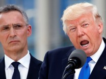 U.S. President Donald Trump speaks beside NATO Secretary General Jens Stoltenberg at the start of the NATO summit at their new headquarters in Brussels