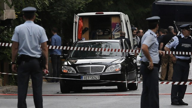 Police secure the area around the car of former Greek prime minister and former central bank chief Lucas Papademos following the detonation of an envelope injuring him and his driver, in Athens