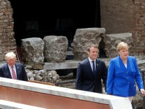 U.S. President Donald Trump walks behind French President Emmanuel Macron and German Chancellor Angela Merkel as they arrive for a family photo during the G7 Summit in Taormina