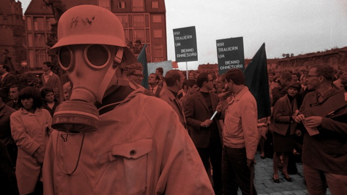 A demonstrator wearing a military gas mask and helmet...