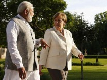 Indian Prime Minister Modi talks to German Chancellor Merkel during their meeting at the German government guesthouse Meseberg Palace in Meseberg