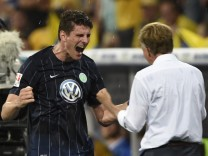 Wolfsburg's Mario Gomez celebrates with coach Andries Jonker as he is substituted