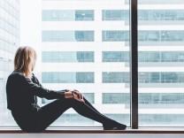 Frau sitzt einsam am Fenster und schaut hinaus