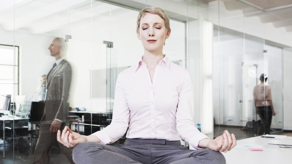 Germany Munich Businesswoman in office meditating on desk model released property released PUBLIC