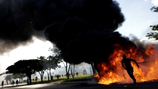 A demonstrator runs near a burning barricade during a protest against President Michel Temer and the latest corruption scandal to hit the country, in Brasilia