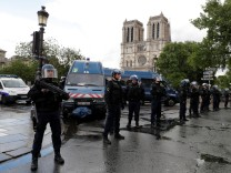 French police stand at the scene of a shooting incident near the Notre Dame Cathedral in Paris