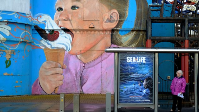 A woman stands at a bus stop in front of a beachside mural in Blackpool, Britain