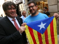 Catalonia's regional President Carles Puigdemont poses with a pro-independence supporter with a Catalan Estelada flag outside the Palau de la Generalitat, the regional government headquarters, in Barcelona