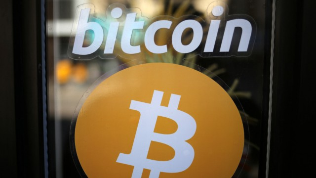 A sign is seen outside a business where a Bitcoin ATM is located in Toronto
