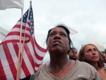 Eine Frau in Puerto Rico hält eine US-Flagge.