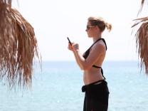 Eine Urlauberin am Strand von Sarti in Griechenland