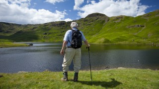 Tourist on nature trail in lakeland countryside at Easedale Tarn lake in the Lake District National
