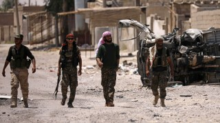 Syrian Democratic Forces (SDF) fighters walk past a damaged vehicle in Raqqa's western neighbourhood of Jazra