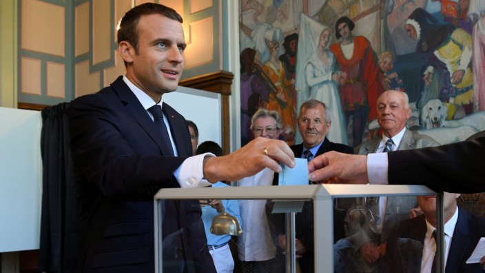 French President Emmanuel Macron casts his ballot as he votes at a polling station in the second round parliamentary elections in Le Touquet