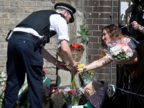 A police officer helps a woman leave flowers near the scene of an attack where a van was driven at muslims outside a mosque in Finsbury Park in North London