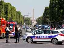 French policemen and firefighters secure the area on the Champs Elysees avenue after an incident in Paris