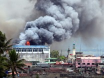 Black smoke comes from a burning building in a commercial area of Osmena street in Marawi city