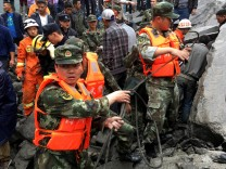Rescue workers work at landslide site that occurred in Xinmo Village