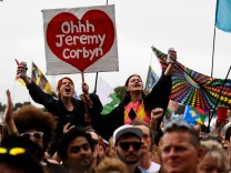 Revellers cheer as Britain's opposition Labour Party Jeremy Corbyn speaks at Worthy Farm in Somerset during the Glastonbury Festival