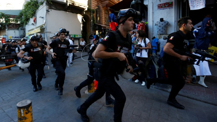 Riot police chase LGBT rights activists as they try to gather for a pride parade in central Istanbul