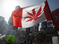 A man waves a flag with a marijuana leaf on it during a rally for the legalization of marijuana in Toronto