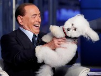 Italy's former PM Berlusconi plays with a dog during the television talk show 'Porta a Porta' in Rome