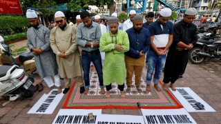 Muslims offer prayers as they take part in a protest in Kolkata