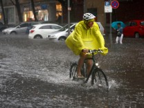 A cyclist rides on a flooded street during heavy rain in Berlin