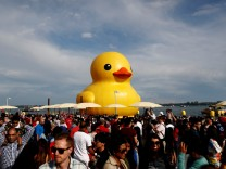 People stand in front of a large inflatable duck installation during 'Canada 150' celebrations in Toronto