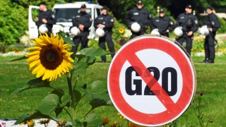 A G20 protest sign is seen in front of a row of police men during a demonstration against the ban of Hamburg's authorities of a G20 protestors camp in the Stadtpark park in Hamburg