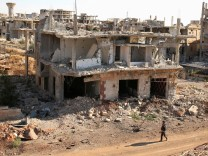 FILE PHOTO: A rebel fighter walks past damaged buildings in a rebel-held part of the southern city of Deraa