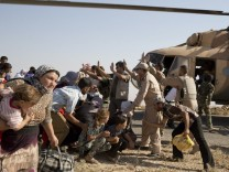 Yezidi refugees wait to board a helicopter sent by the Kurdish autonomous government to Iraq?s Sinjar mountains.