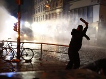 A protester throws a bottle towards riot police during demonstrations at the G20 summit in Hamburg