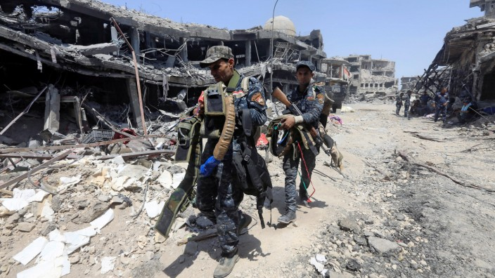 Members of Iraqi Federal police carry suicide belts used by Islamic State militants in the Old City of Mosul