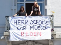 Residents are seen behind a banner reading 'Mr. Scholz, we have to talk' during a 'Clean-up' after demonstrations at the G20 summit in the Sternschanze district in Hamburg